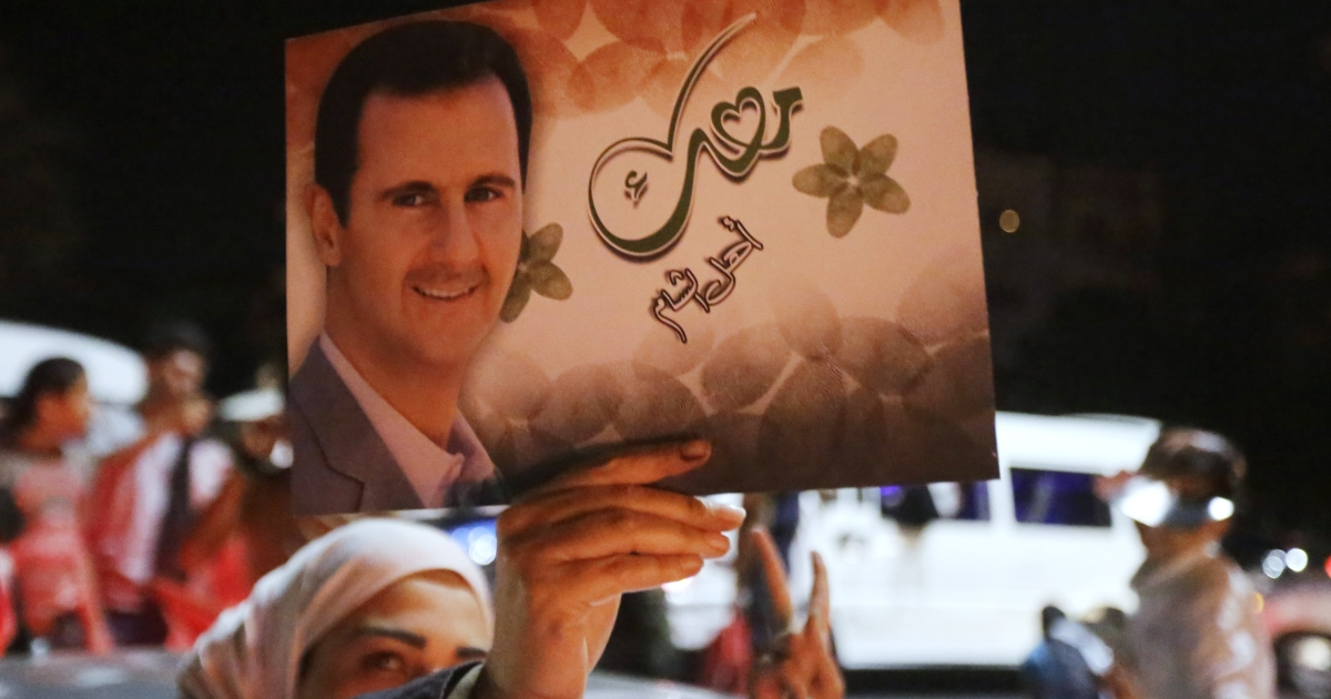 A woman holds a picture of re-elected Syrian President Bashar al-Assad as she celebrates in Damascus.</p>