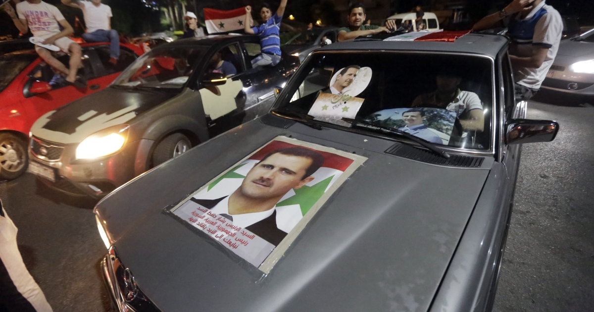 Syrians celebrate in a car with a picture of re-elected Syrian President Bashar al-Assad in Damascus.</p>