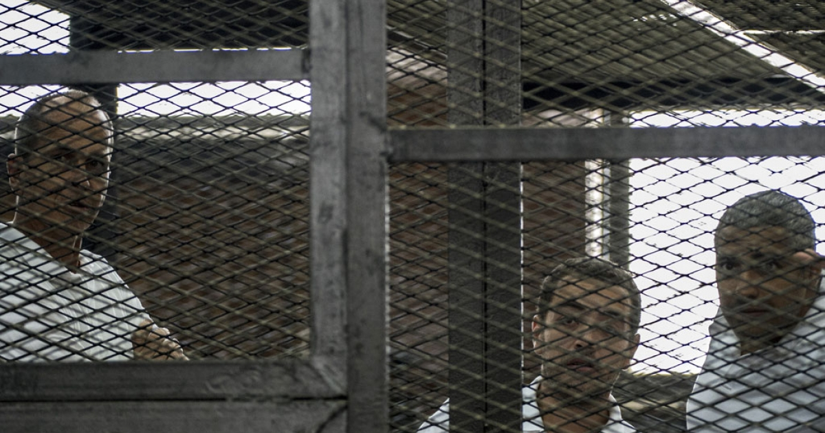 Al Jazeera news channel's Australian journalist Peter Greste (L) and his colleagues, Egyptian-Canadian Mohamed Fadel Fahmy (R) and Egyptian Baher Mohamed (C), listen to the verdict inside the defendants' cage at the police institute near Cairo's Tora prison.</p>