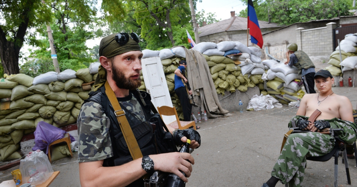 Pro-Russian armed separatist militants stand guard at a barricade in Mariupol, on June 9, 2014.</p>