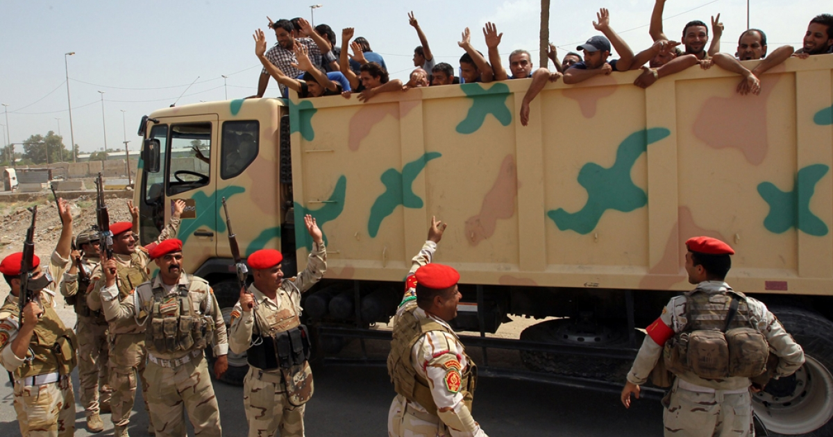 Iraqi men who volunteered to join the fight against a major offensive by jihadists in northern Iraq wave to soldiers from the back of an army truck as they leave a recruiting center in the capital Baghdad on June 13, 2014.</p>