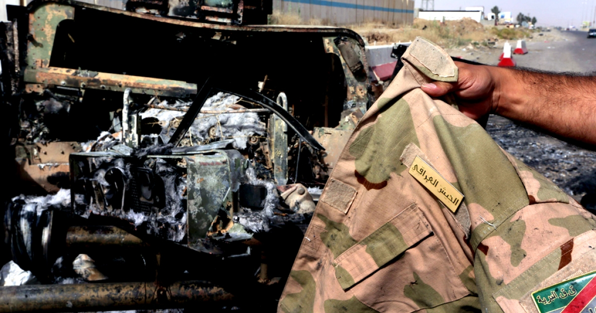 A man displays an Iraqi army jacket in front of a burnt out US-made Iraqi army Humvee vehicle east of the city of Mosul, on June 11, 2014, a day after Sunni militants including fighters from the Islamic State of Iraq and the Levant (ISIL) overran the city.</p>