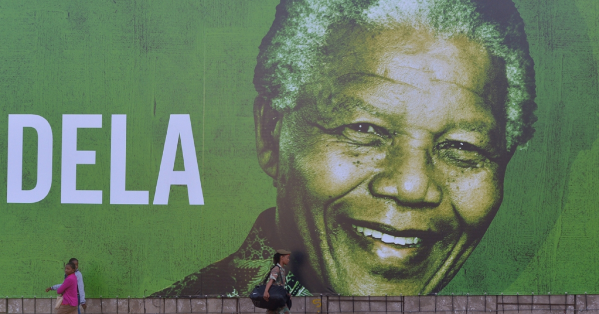 A soldier walks past a giant banner of South African former president Nelson Mandela on Dec. 14, 2013 in Pretoria.</p>