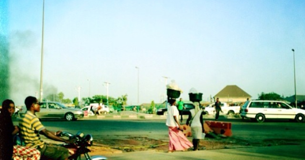 Women walk in Nyanya near the site of the two bomb attacks.</p>