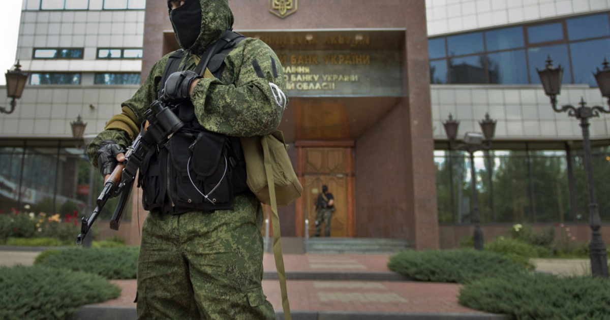 A pro-Russian rebel stands guard outside a local branch of the National Bank of Ukraine after seizing the building in Donetsk, eastern Ukraine, on June 16, 2014.</p>