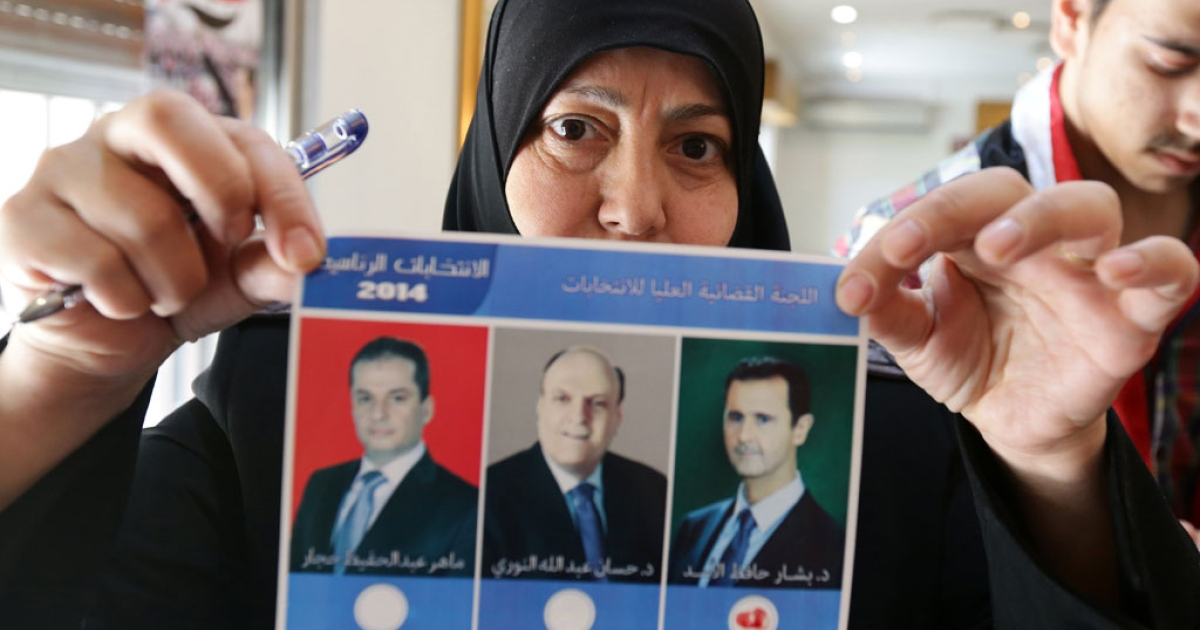 A Syrian woman shows a ballot paper bearing the portraits of the three presidential candidates at a polling station in central Damascus on June 3, 2014.</p>