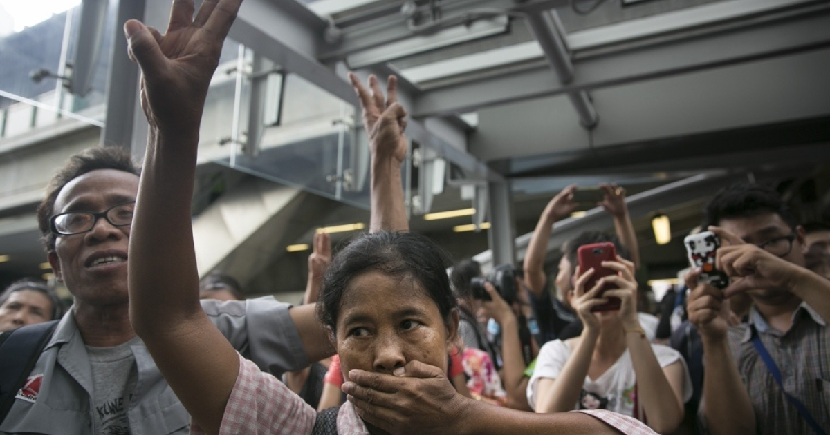Thai protesters flash the 'Hunger Games' salute at a demonstration before military police shut them down outside a shopping mall on June 1, 2014 in Bangkok, Thailand.</p>