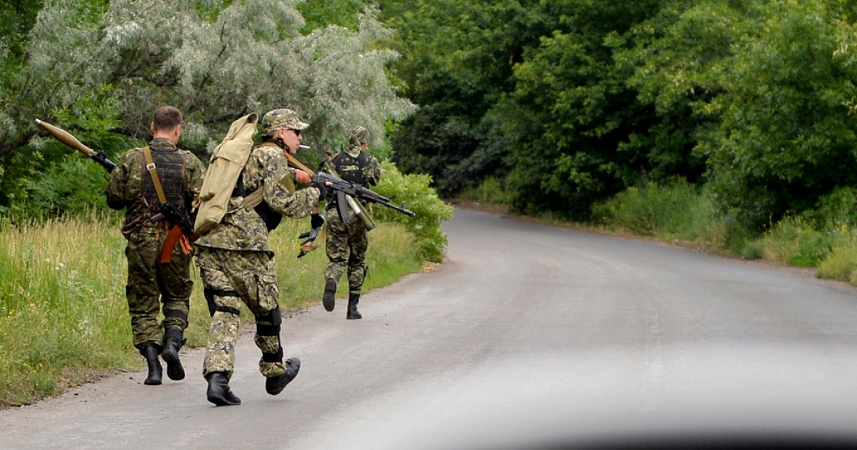 Pro-Russian armed militiamen take up positions on a secondary road between Kramatorsk and Slovyansk, on June 11, 2014.</p>