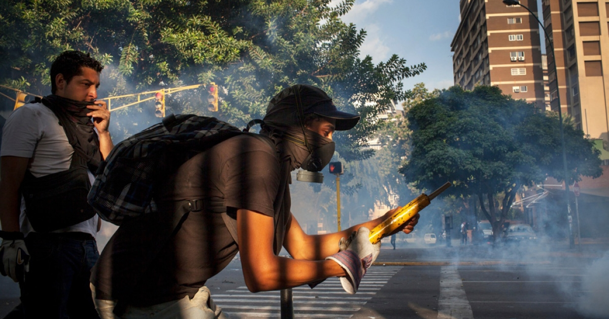 A protester returns tear gas fire with fireworks aimed at the National Police. A month into a wave of unrest that has spread across Venezuela, protests continued daily in the upper class enclave of Altamira, Caracas, as well as other parts of the city and country.</p>
