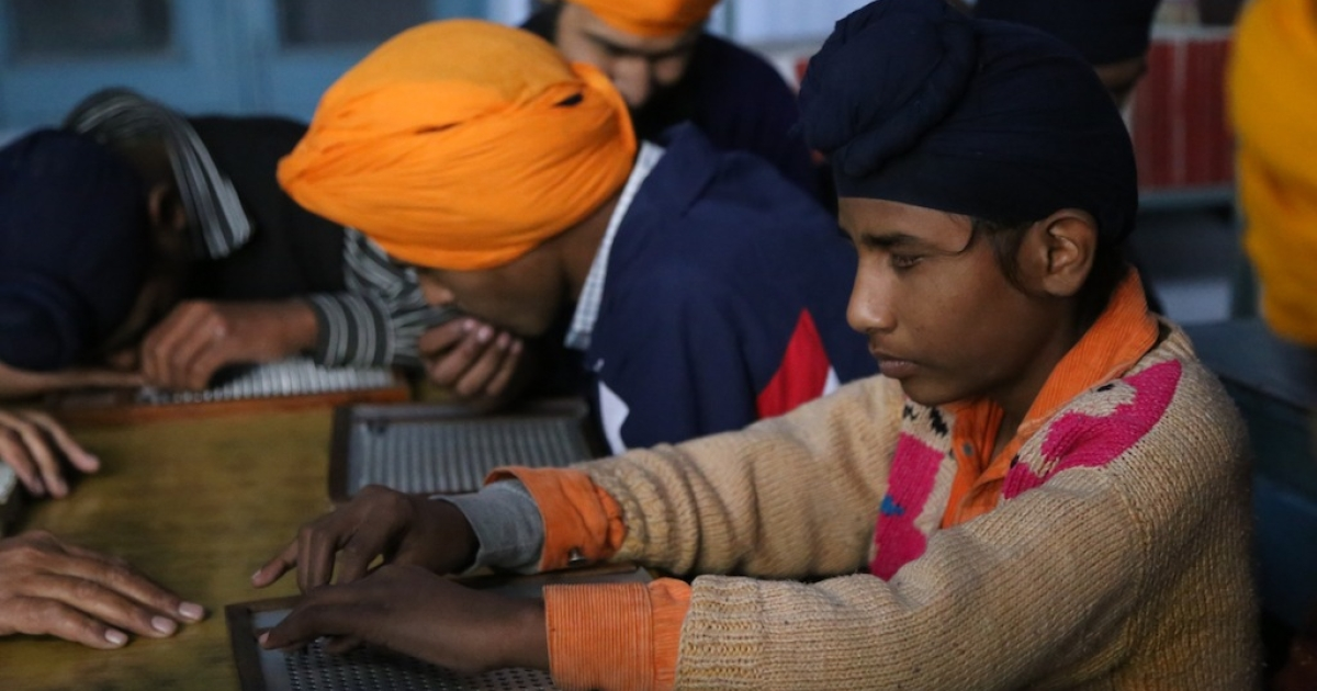 Paras, an 11-year-old boy, reads a book by moving his fingers along the text in Braille at the school for the blind, Central Khalsa Orphanage, Amritsar India in January 2014.</p>