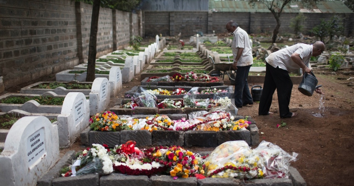 A cemetery worker washes his hands next to 5 fresh graves after the funeral ceremony of Ruhila Adatia Sood, A Radio Africa television and radio presenter, on September 26, 2013 in Nairobi, Kenya. The country is observing three days of national mourning as security forces begin the task of clearing and securing the Westgate shopping mall following a four-day siege by militants.</p>
