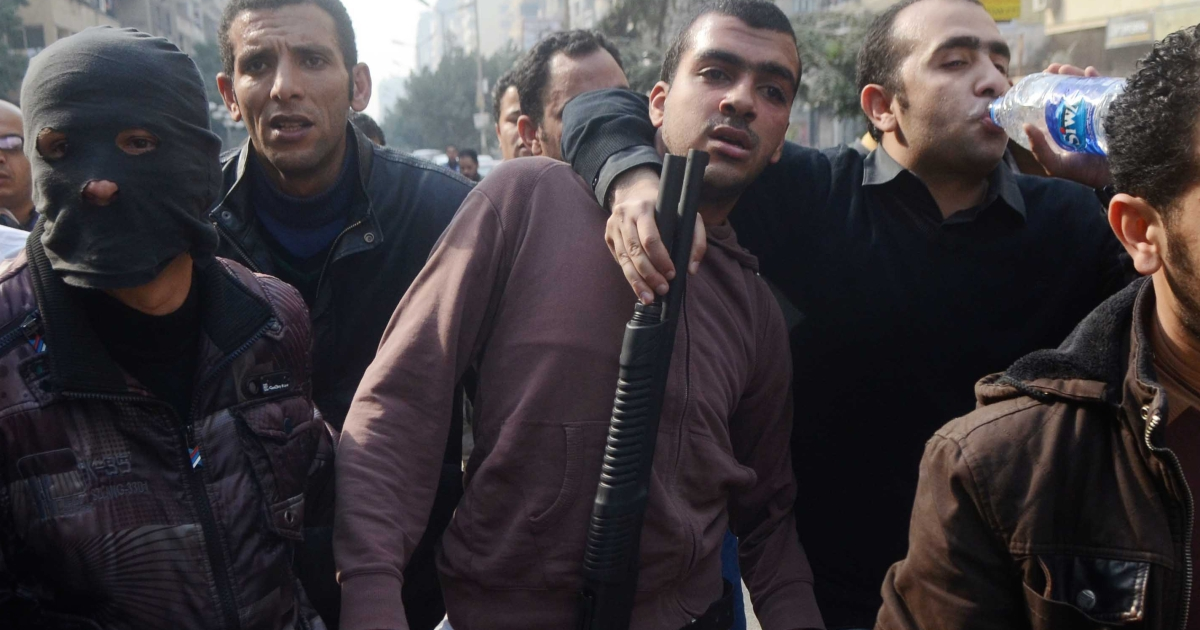 Egyptian police arrest a Muslim Brotherhood supporter (C) following a demonstration in the Nasr City district of Cairo, on January 25, 2014. Police fired tear gas at anti-government protesters as the country marked the anniversary of a 2011 uprising that overthrew veteran president Hosni Mubarak.</p>