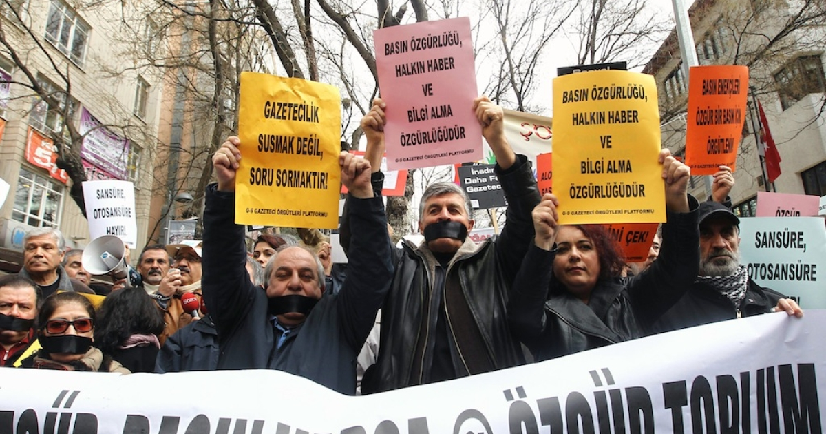 Demonstrators wearing black ribbon over their mouths hold up posters as journalists demanding freedom for the media take part in a protest against Turkey's ruling Justice and Development Party (AKP) in Ankara on February 15, 2014. Signs read: