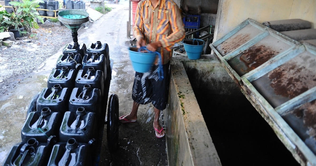 A man fills a jerry can with clean water on World Water Day March 22, 2014 in Surabaya, Indonesia. World Water Day recognizes the global need for water and energy conservation.</p>