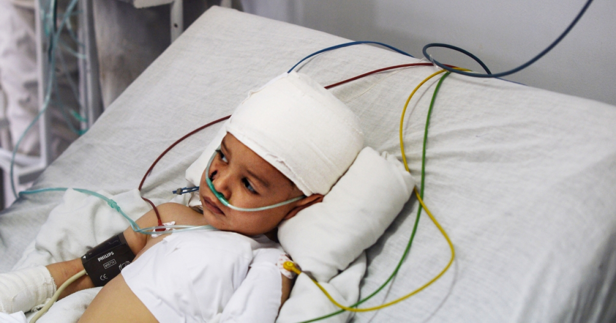 Abuzar Ahmad, the only surviving child of Afghan journalist Sardar Ahmad, who was killed with his wife and two other children in an attack at a Kabul hotel, lies in bed in the intensive care unit of a local hospital on March 24, 2014.</p>