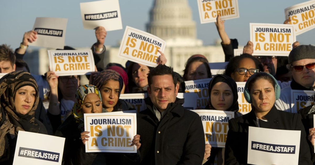 Employees and supporters of the television network Al Jazeera hold up signs as they protest the imprisonment of Al Jazeera journalists in Egypt, at the Newseum, near the US Capitol, in Washington, DC, Feb. 27, 2014.</p>