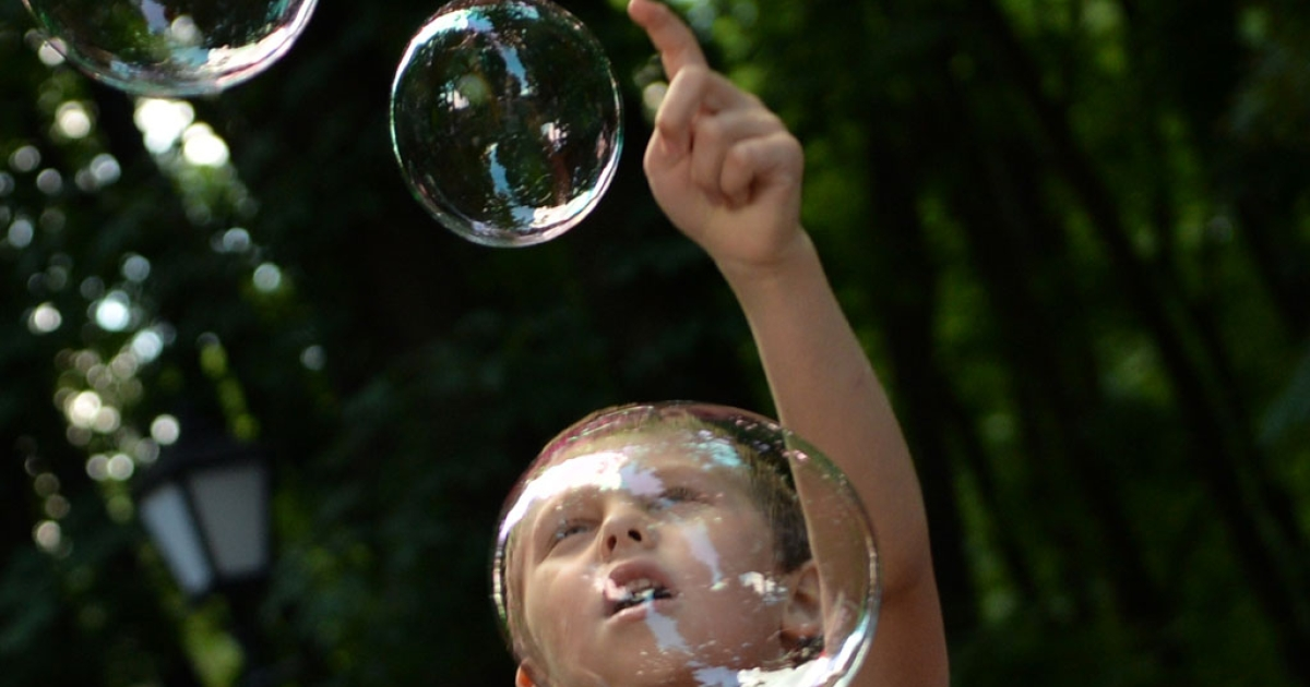 A boy plays with soap bubbles during a charity event organized by a motorcycle club for children with autism in Kiev, Ukraine, on May 28, 2013.</p>