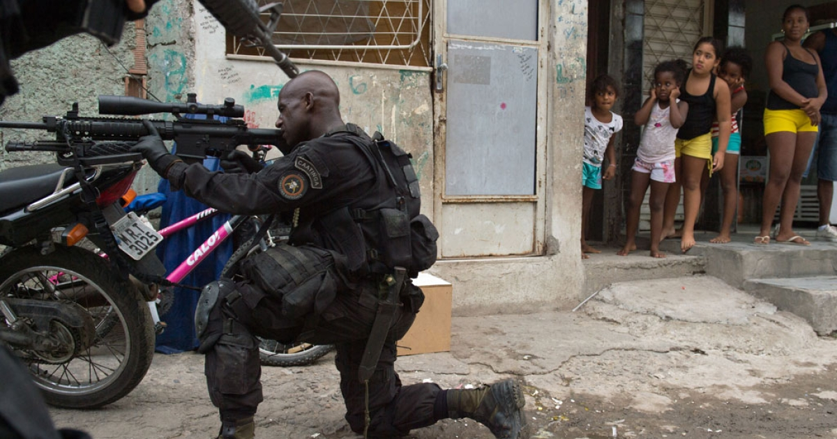A group of girls watch how a PM paramilitary police BOPE special unit sniper secures the area as Brazilian soldiers (not framed) conduct a search for weapons in the Favela da Mare slum complex in the northern suburbs of Rio de Janeiro, Brazil on March 26, 2014.</p>
