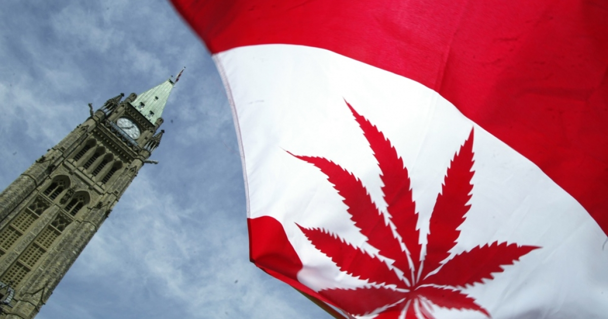 A Canadian flag with a marijuana leaf flies alongside Parliament Hill in Ottawa, Canada during a pot legalization rally.</p>