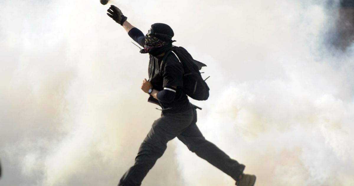 An opposition activist throws a tear gas canister back at the the national police in Caracas on March 10.</p>