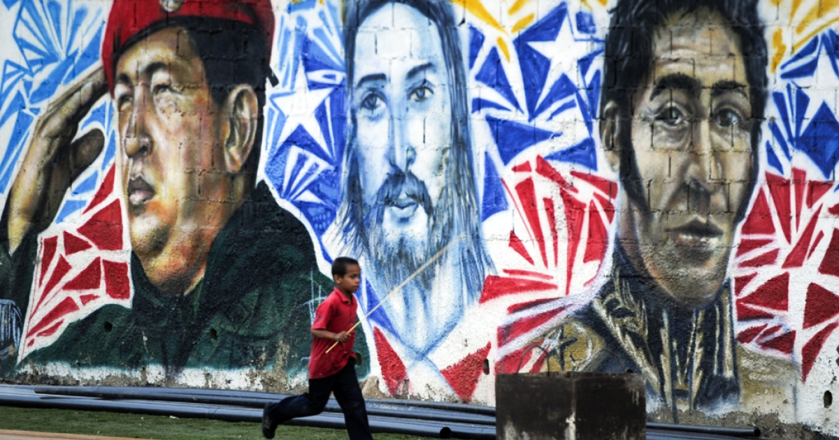 A boy runs next to a mural paint depicting late Venezuelan President Hugo Chavez (L), Jesus Christ and Latin American Independence Hero Simon Bolivar in Caracas.</p>
