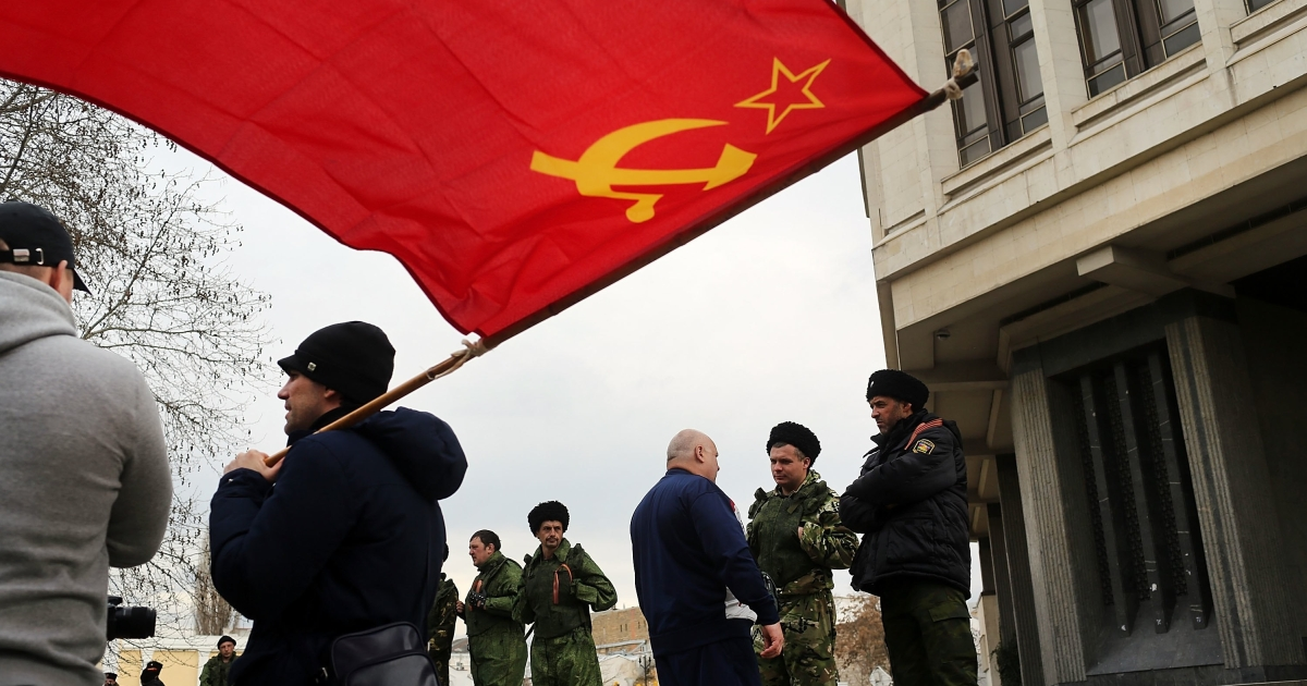 A Soviet-era flag flies as dozens of Cossacks surround the Crimean parliament, where legislators have voted to join Russia.</p>