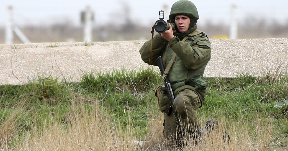 A soldier under Russian command aims a rocket propelled grenade launcher at a group of over 100 hundred unarmed Ukrainian troops who appeared at the Belbek airbase, which the Russian troops are occupying, in Crimea on March 4, 2014 in Lubimovka, Ukraine.</p>
