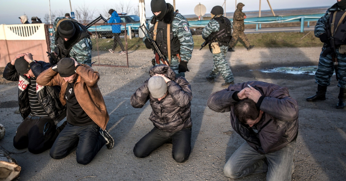 Pro-Russia gunmen search people at a checkpoint at Crimea's new de facto border with the rest of Ukraine.</p>
