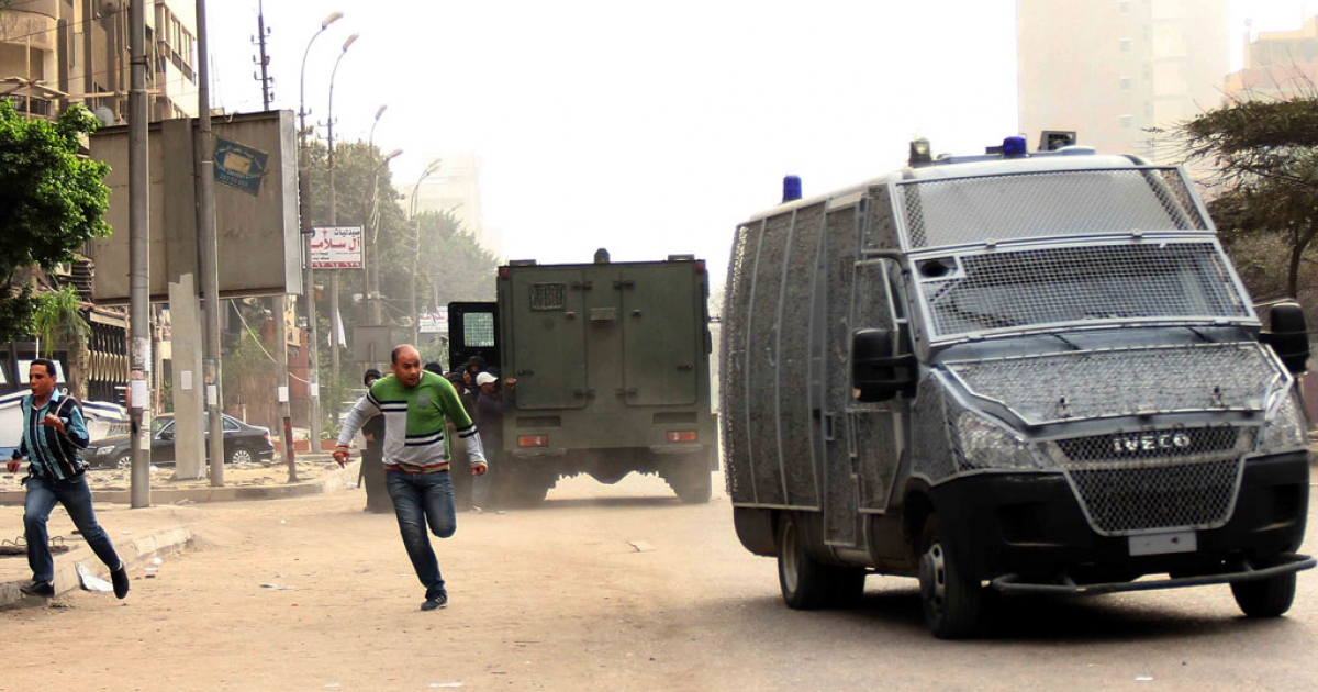 Egyptian protestors run for covers near police vehicles during clashes with Egyptian police following a demonstration in support of the Muslim Brotherhood and Egypt's ousted president Mohamed Morsi in the Ain Shams district of the capital Cairo on March 7, 2014.</p>