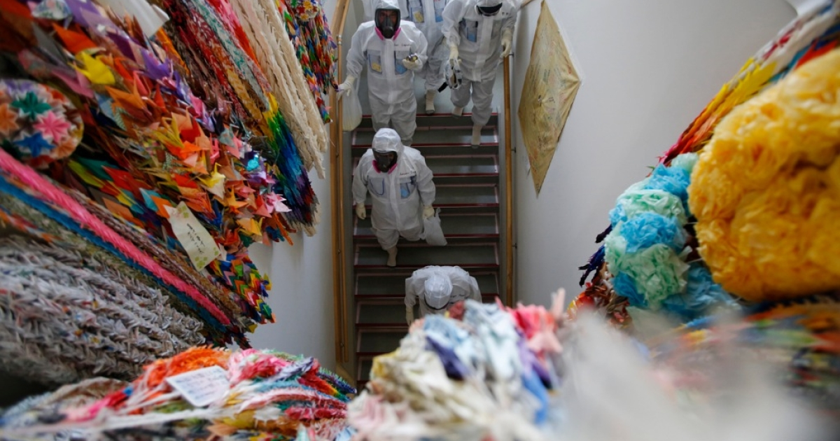 Members of the media and Tokyo Electric Power Co. (TEPCO) employees wearing protective suits and masks walk alongside a wall lined with thousands of paper cranes inside the main anti-earthquake building at the tsunami-crippled TEPCO Fukushima Daiichi nuclear power plant on March 10, 2014. Members of the media were allowed into the plant a day before the third anniversary of the March 11, 2011 earthquake and tsunami, which triggered the world's worst nuclear crisis since Chernobyl.</p>