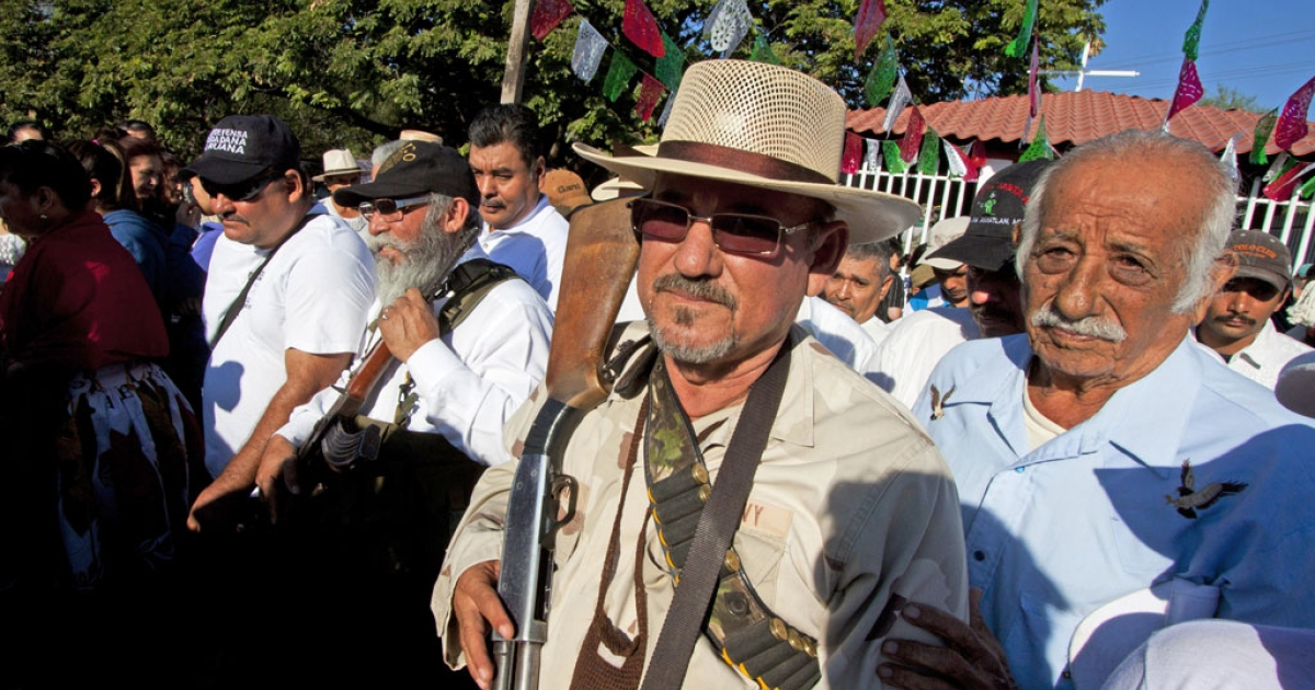 Hipolito Mora (C), leader of the self-protection militia walks in La Ruana community, state of Michoacan, Mexico, on Feb. 24, 2014.</p>