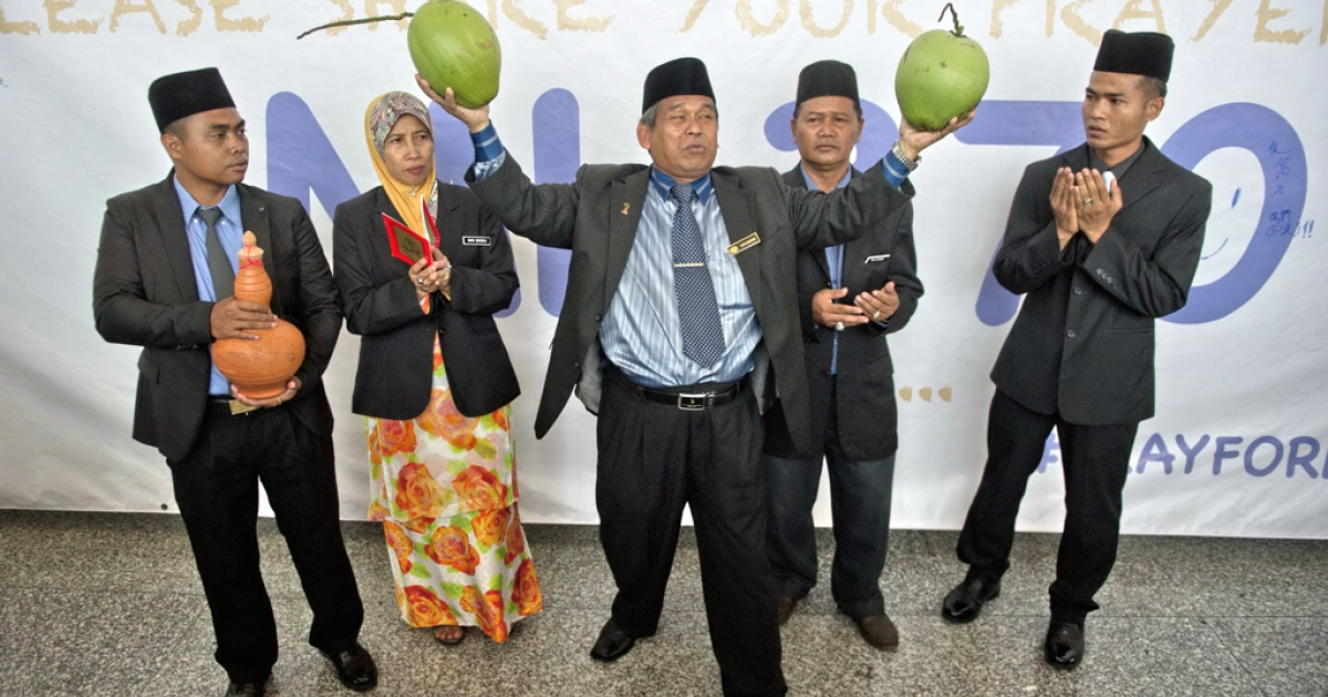 A well-known Malaysian shaman, Ibrahim Mat Zin (C) holds two coconuts as him and his assistants offer to locate the missing Malaysia Airlines Flight 370 plane using a spiritual method and prayer at the Kuala Lumpur International Airport (KLIA) in Sepang on March 12, 2014.</p>