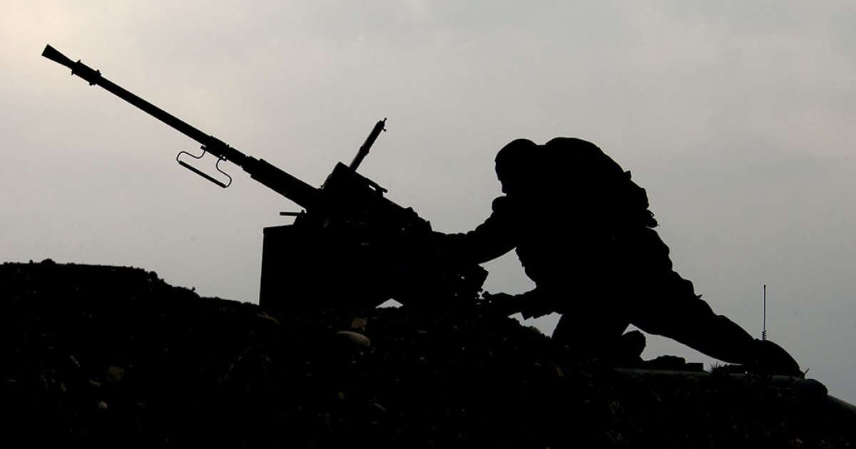 An Israeli soldier checks his machine gun mounted on an army vehicle stationed on the border between Israel and the Gaza Strip on March 13, 2014.</p>