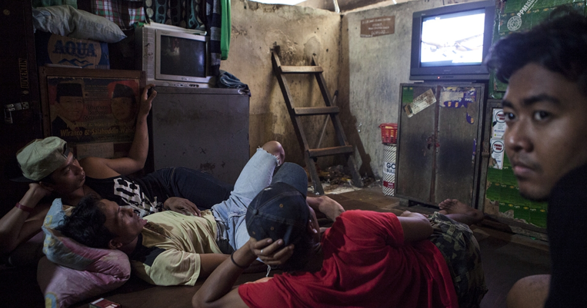 On a platform under the Kuningan bridge in Jakarta, as six lanes of traffic pass overhead, bridge dwellers watch TV and play games in what they call the living room. Those who don't have their own room sleep here at night.</p>