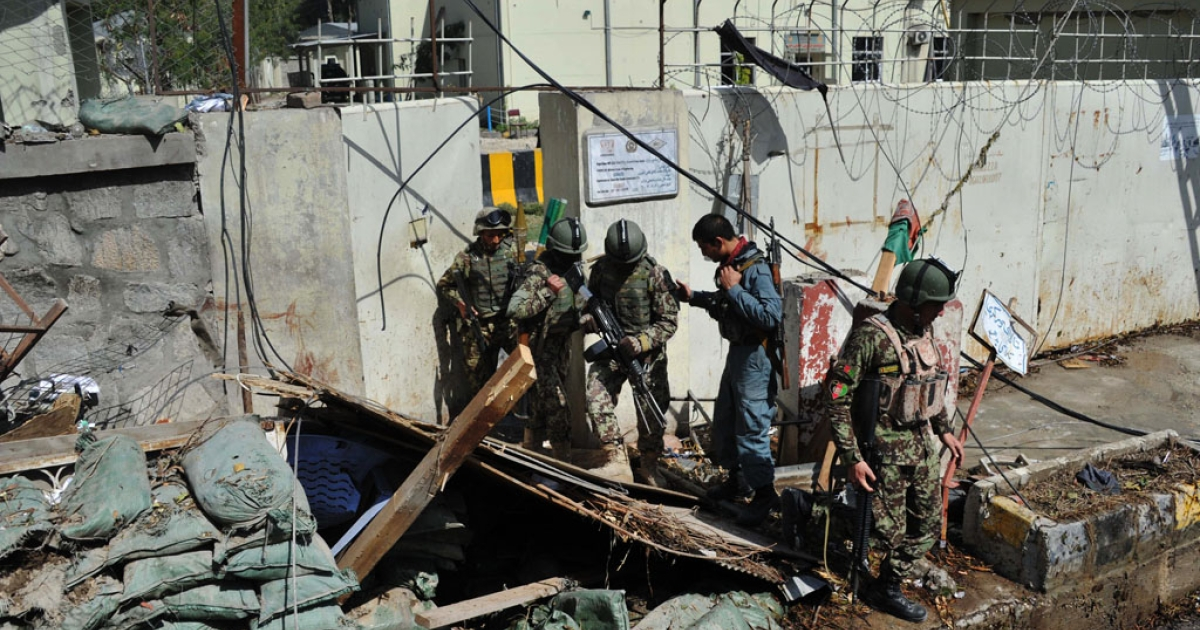 Afghan soldiers exit through the partially demolished gate of a police station which was the scene of an attack in Jalalabad on March 20, 2014. At least six Taliban suicide attackers stormed a police station in the centre of the eastern Afghan city of Jalalabad, killing three people in a major assault ahead of the presidential election.</p>