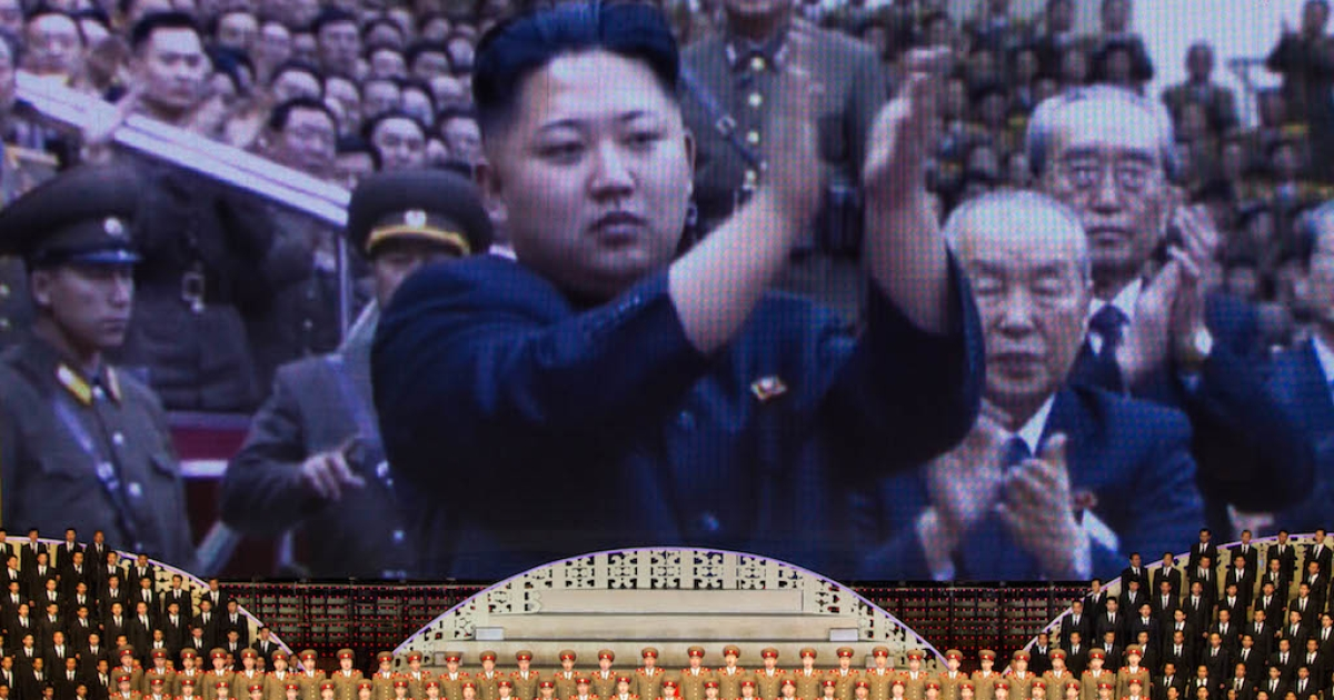 North Korean performers sit beneath a screen showing images of leader Kim Jong-Un at a theatre during celebrations to mark the 100th birth anniversary of the country's founding leader Kim Il-Sung, in Pyongyang on April 16, 2012.</p>