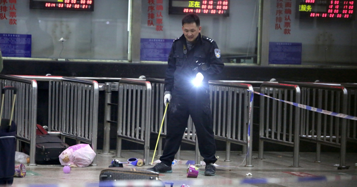 A police investigator inspects the scene of an attack at a railway station in Kunming, Yunnan, on March 2, 2014. A mass stabbing at a Chinese train station late on March 1 left 28 people dead and 113 injured in a