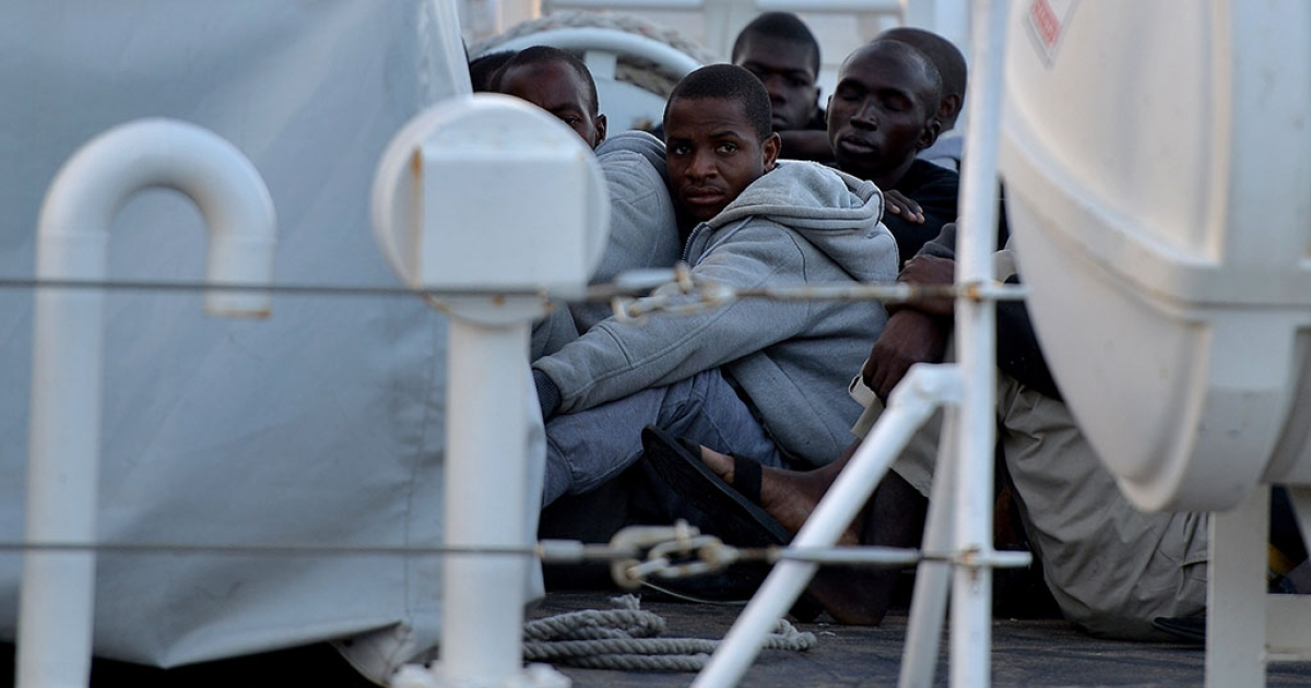Some 100 migrants sit on the Guardia Costiera boat after being rescued off the shores of the island of Lampedusa on October 25, 2013.</p>