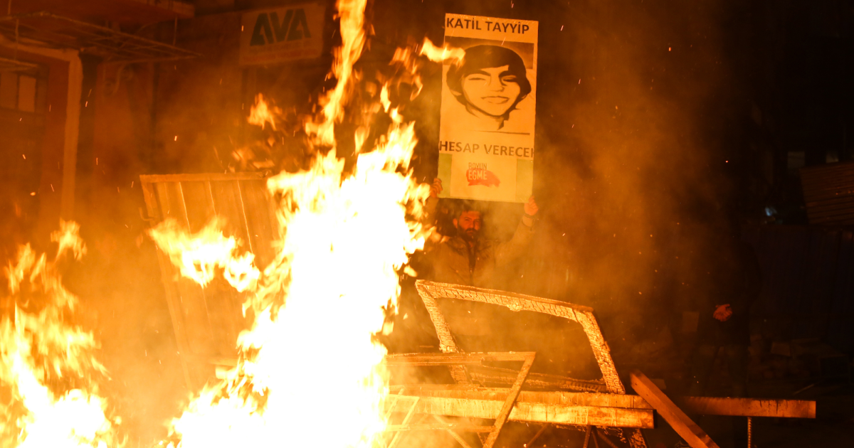 A protester holds a portrait of Berkin Elvan, the 15-year-old boy who died from injuries suffered during last year's anti-government protests, during clashes between police and demonstrators after the funeral of Elvan, in Istanbul on March 12, 2014.</p>