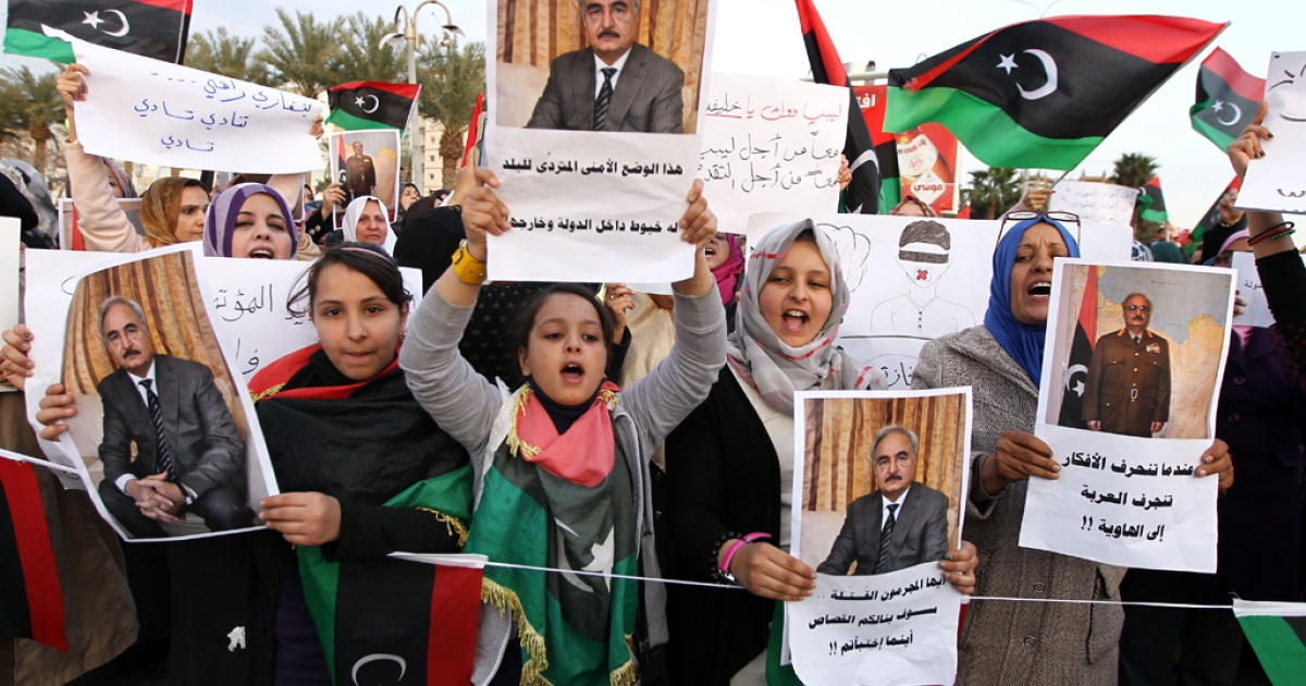 Libyan protestors wave their national flag and hold pictures of Libya's Major Gen. Halifa Haftar during demonstrations calling for him to stand down and against the extended mandate of the General National Congress (GNC), the country's highest political authority, in Benghazi on Feb. 28, 2014.</p>