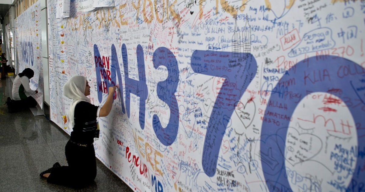 A Malaysia Airlines employee writes a message expressing prayers and well-wishes for passengers onboard missing Malaysia Airlines (MAS) flight MH370 at Kuala Lumpur International Airport in Sepang on March 14, 2014.</p>