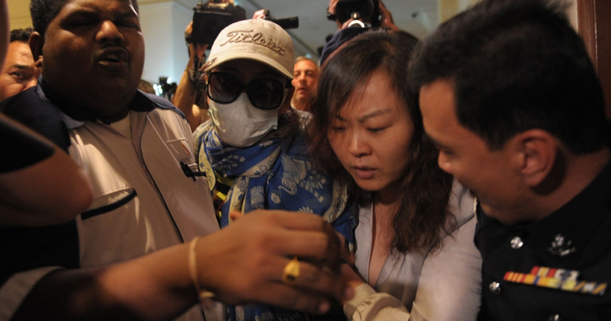Chinese relatives of passengers from the missing Malaysia Airlines flight MH370 are stopped and escorted away by Malaysian police from entering the media center before the start of a press conference at a hotel near Kuala Lumpur International Airport (KLIA) in Sepang, outside Kuala Lumpur on March 19, 2014.</p>
