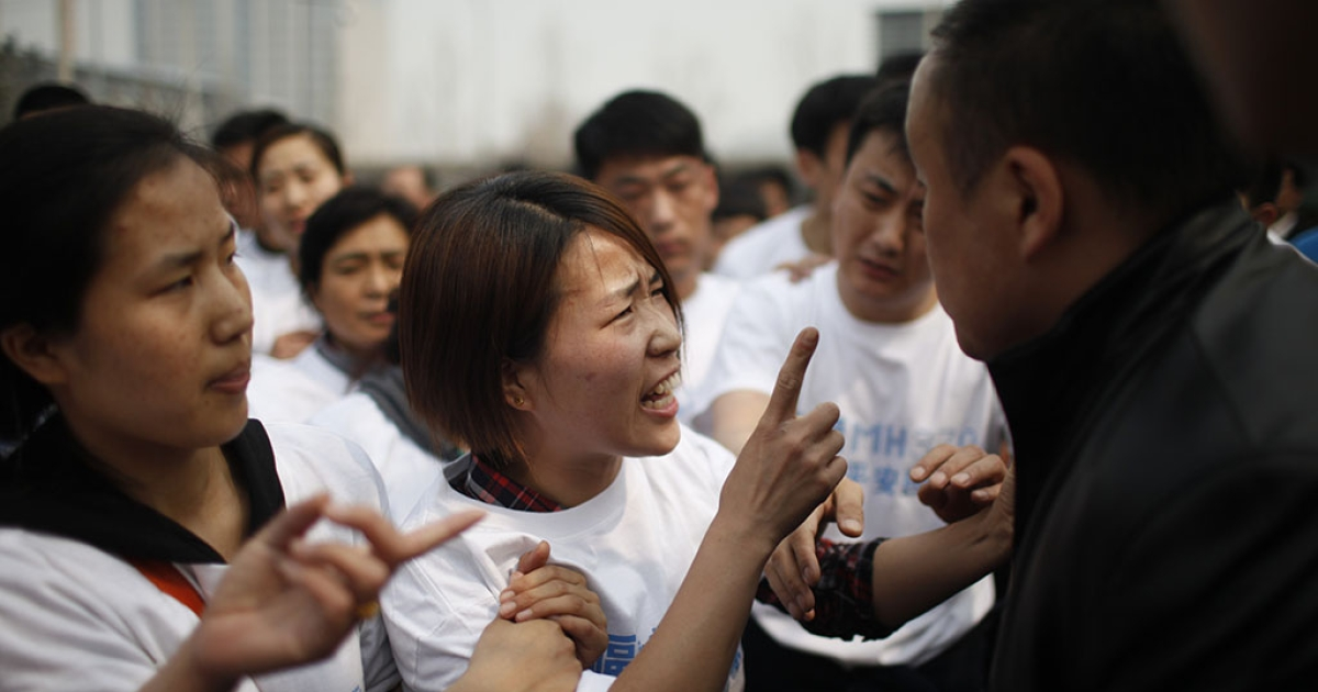 A relative (C) of passengers on missing Malaysia Airlines flight MH370 yells at a security personnel (R) while she attends a protest outside the Malaysian embassy in Beijing on March 25, 2014.</p>
