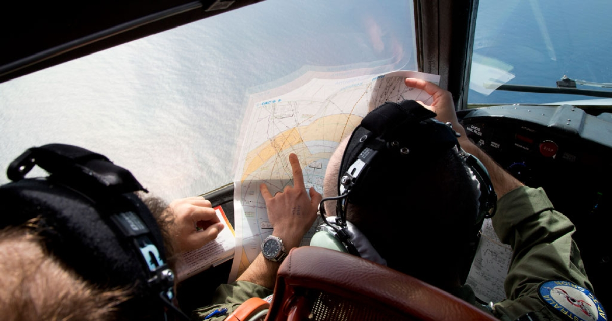 Flight Lieutenant Jayson Nichols looks at a map as he flies aboard a Royal Australian Air Force AP-3C Orion aircraft searching for missing Malaysian Airlines flight MH370 over the southern Indian Ocean on March 27, 2014 off the coast of Perth, Australia.</p>