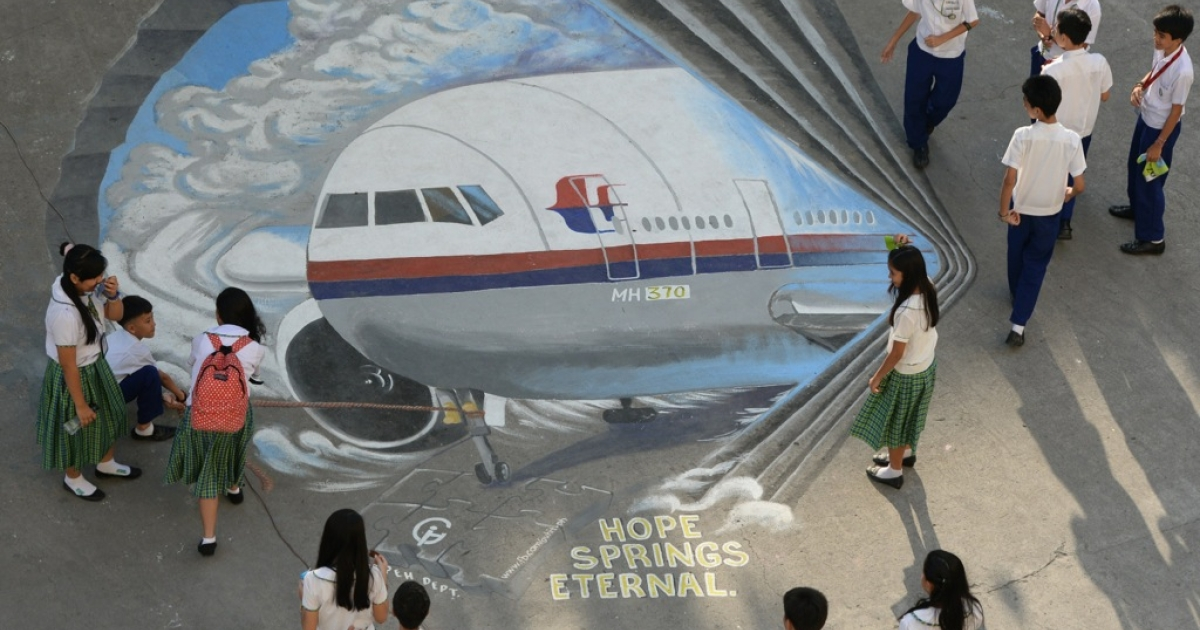 Students stand next to a giant mural featuring missing Malaysia Airlines flight MH370 displayed on the grounds of their school in Manila's financial district of Makati on March 18, 2014.</p>