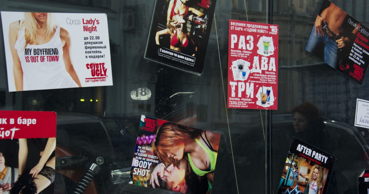 A Russian woman is reflected in a window as she walks past nightclub posters in Moscow on March 3, 2012.</p>