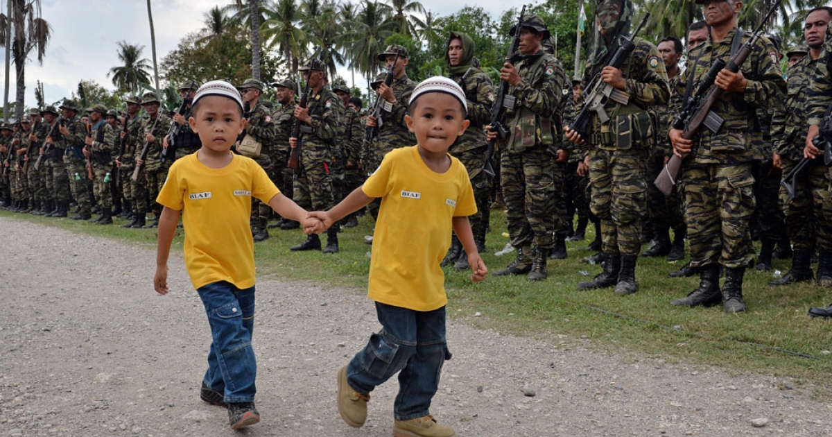 Two young boys walk past Moro Islamic Liberation Front (MILF) rebels, lined up in formation, during a rally in support of the peace signing agreement at Camp Darapanan in the town of Sultan Kudarat on the southern Philippine island of Mindanao on March 27, 2014.</p>