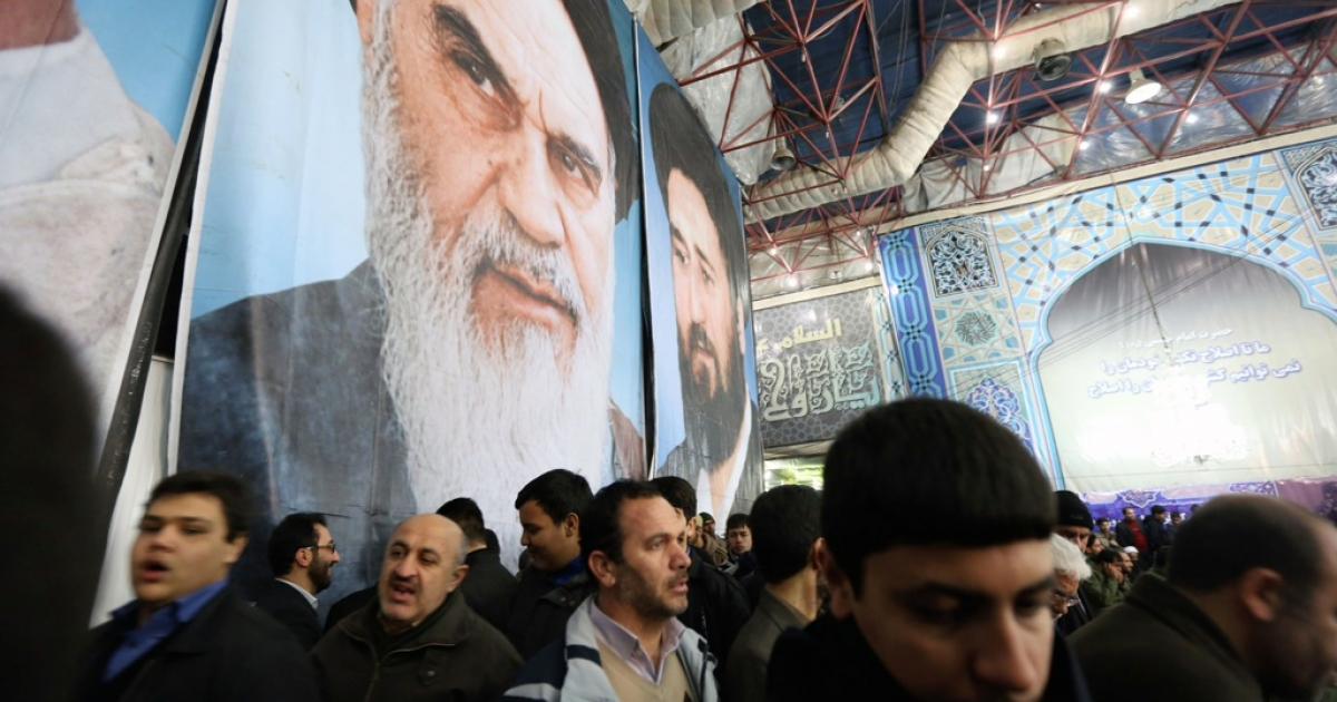 Iranian men gather in front of a giant portrait of the founder of Iran's Islamic Republic, Ayatollah Ruhollah Khomeini on February 1, 2014 at Khomeini's mausoleum in a suburb of Tehran during the festivities marking the 35th anniversary of his return from exile. Khomeini returned from exile in 1979, the trigger for a revolution which spawned an Islamic state now engulfed in a deep political crisis. AFP PHOTO/ATTA KENARE        (Photo credit should read ATTA KENARE/AFP/Getty Images)</p>