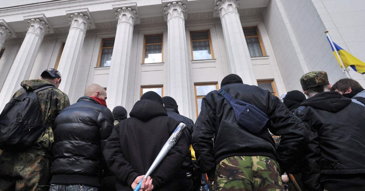 Supporters of the right-wing nationalist party Pravy Sector (Right Sector), one of them carrying a baseball bat, protest in front of the Ukrainian Parliament in Kyiv on March 28, 2014.</p>
