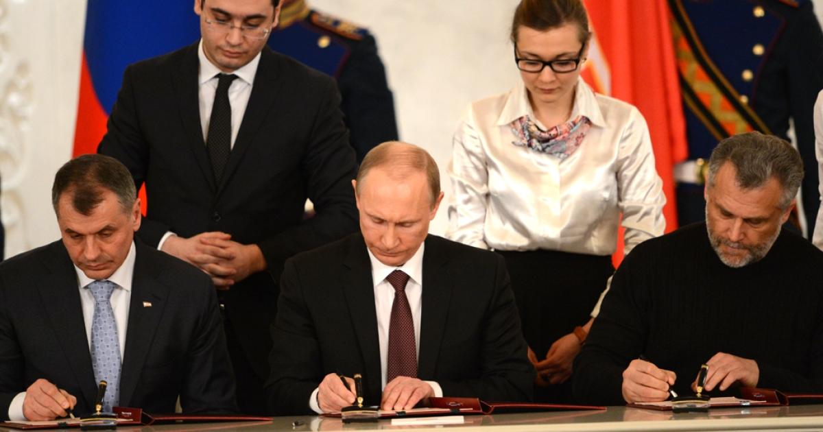 Russia's President Vladimir Putin (C),  Crimean parliament speaker Vladimir Konstantionov (L)  and Alexei Chaly, Sevastopol's new de facto mayor (R), sign a treaty on the Ukrainian Black Sea peninsula becoming part of Russia in the Kremlin in Moscow on March 18, 2014.</p>